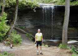 Cyclist in front of the main waterfall at Fall Hollow Waterfall.