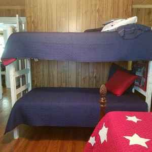 Patriotic Room with a full size bed, bunk twin beds, table and chairs and a baby crib.