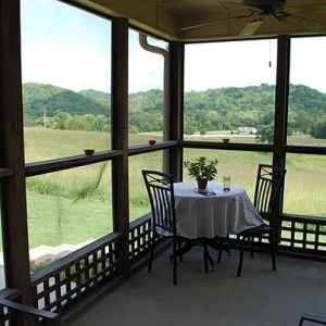 Screened-in porch wraps around three sides of the bed and breakfast.