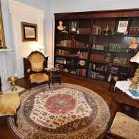 The Library - the secluded library with mahogany bookshelves filled with antique books and a grand marble fireplace.