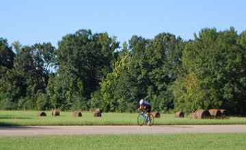 Bicyclist riding past Bear Creek Mound.