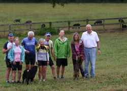 Cyclists posing with Farmhouse Sanctuary innkeepers and a few of their four-legged full-time guests.