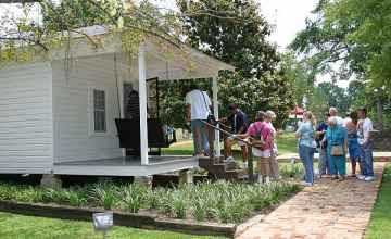 A group of Elvis fans visiting his birthplace home.